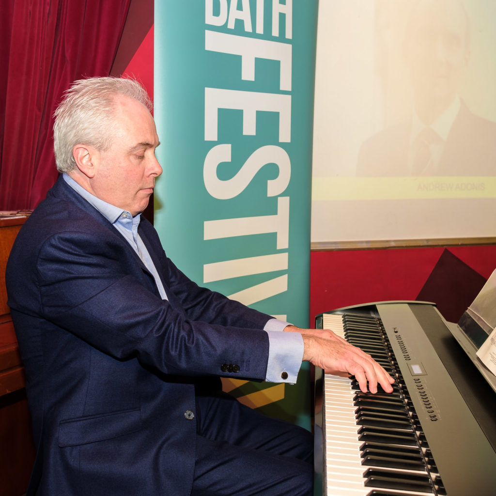 Corporate event photography with pianist entertaining crowd at the Bath Festival