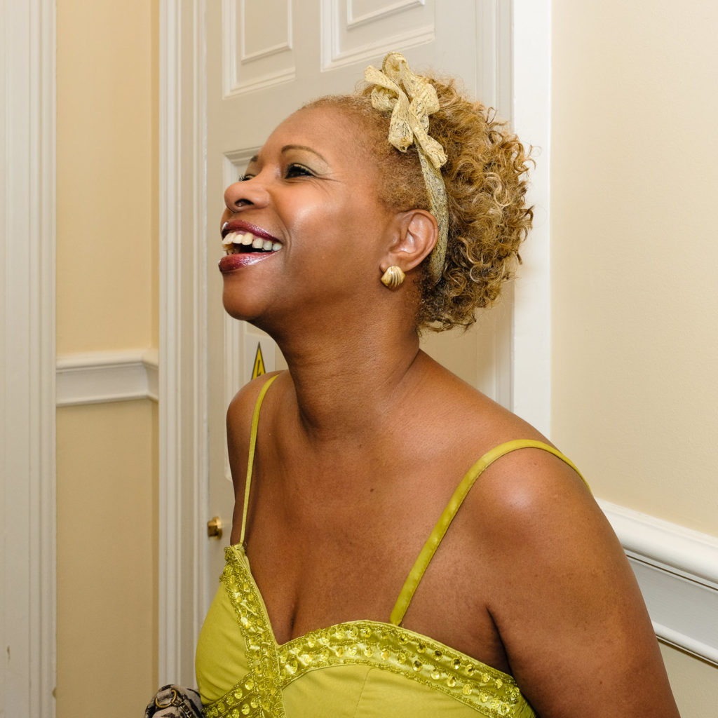Corporate event photography -with smiling female guest wearing evening dress