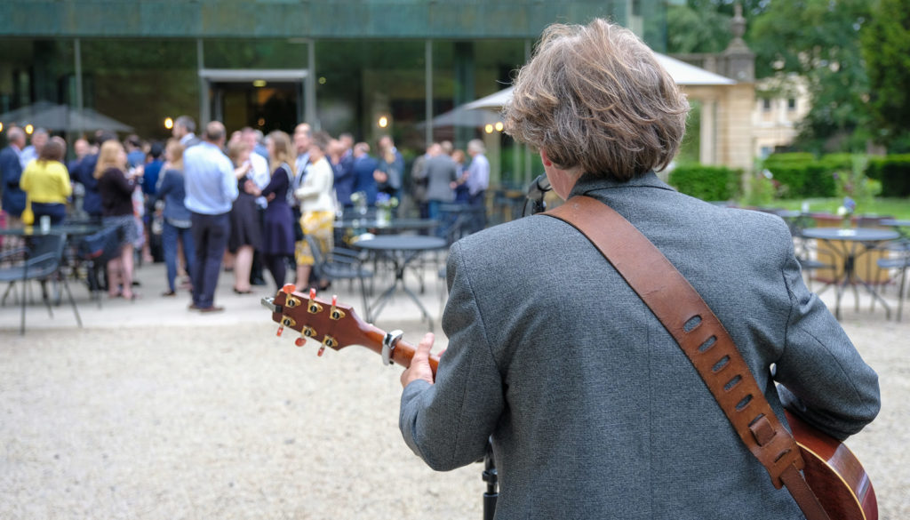 Corporate event photography - singer and guitarist playing to crowd at Holburne museum in Bath