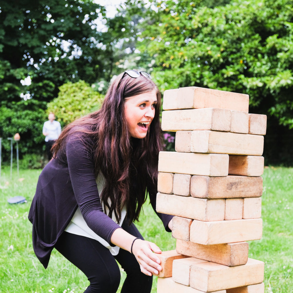 Corporate event photography - lady playing with giant outdoor Jenga