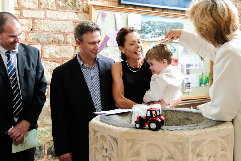 Special occasion family photography - mother and father with their son by the font at church christening