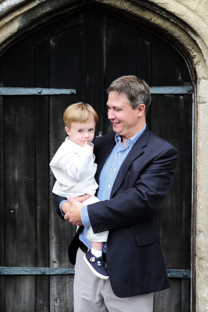 Special occasion family photography - father holding his son outside church at christening