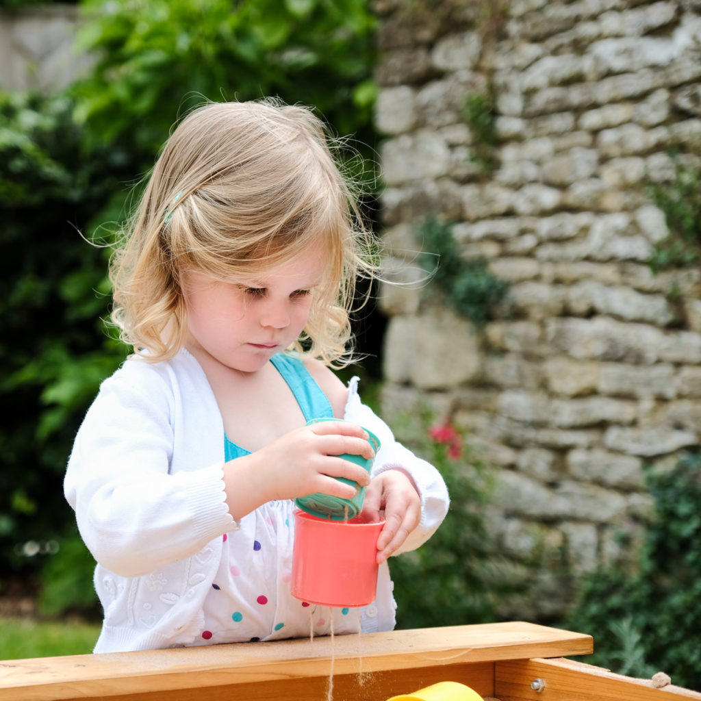 Special occasion family photography - young girl playing in the garden at christening