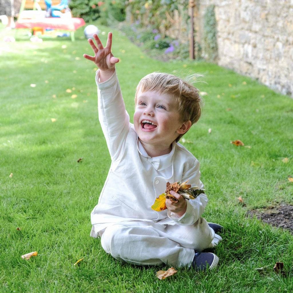 Special occasion family photography - young boy in white linen outfit playing in the garden at his christening