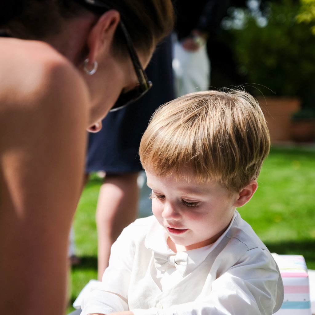 Special occasion family photography - young boy receiving gift at Christening
