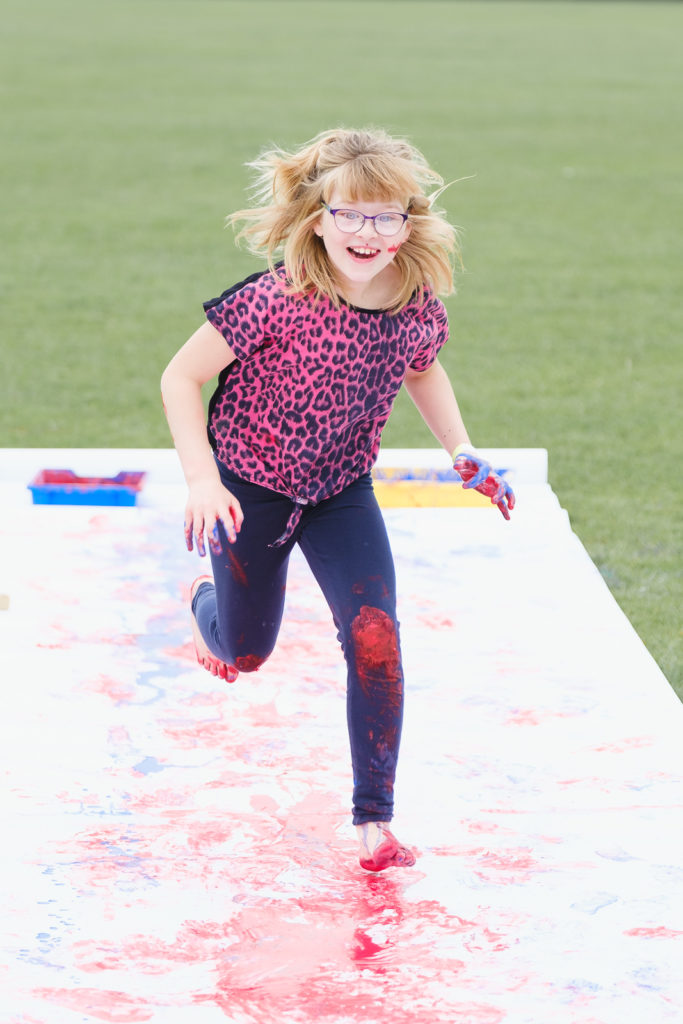 Young girl having fun with paint sliding at the Try Games 2019