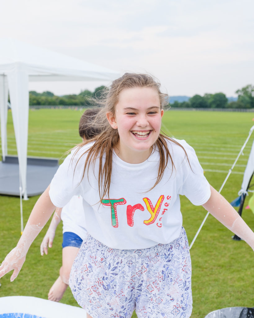 Teenage girl having fun in the custard pool at the Try Games 2019