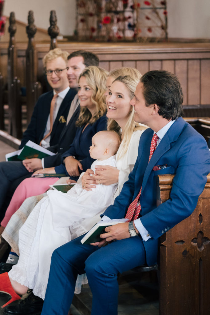 Special occasion photography with family together and smiling during christening service