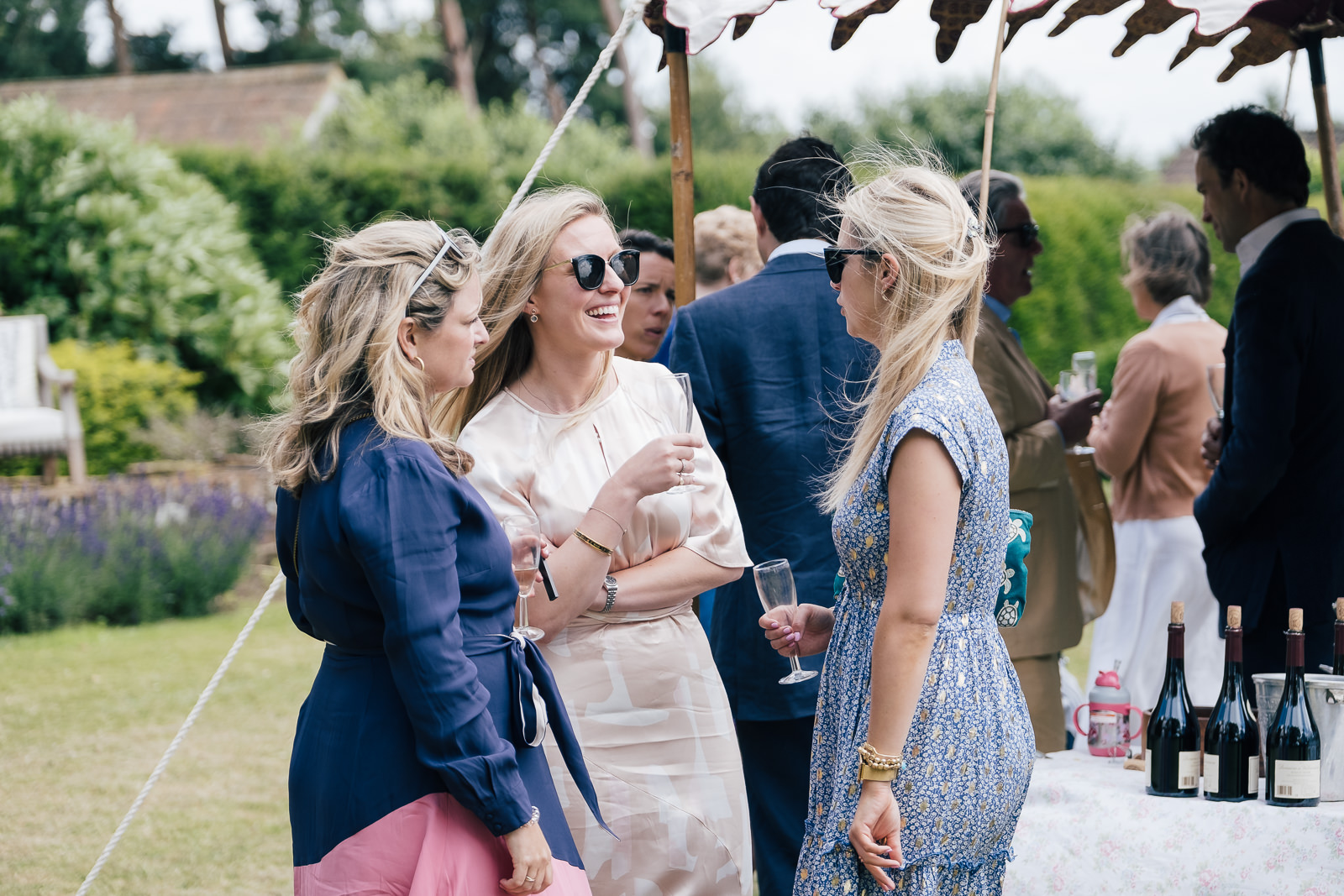Special occasion photography with guests chatting at summer christening celebration