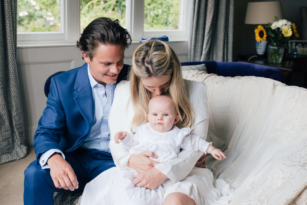 Special occasion photography with young family cuddling their child at christening