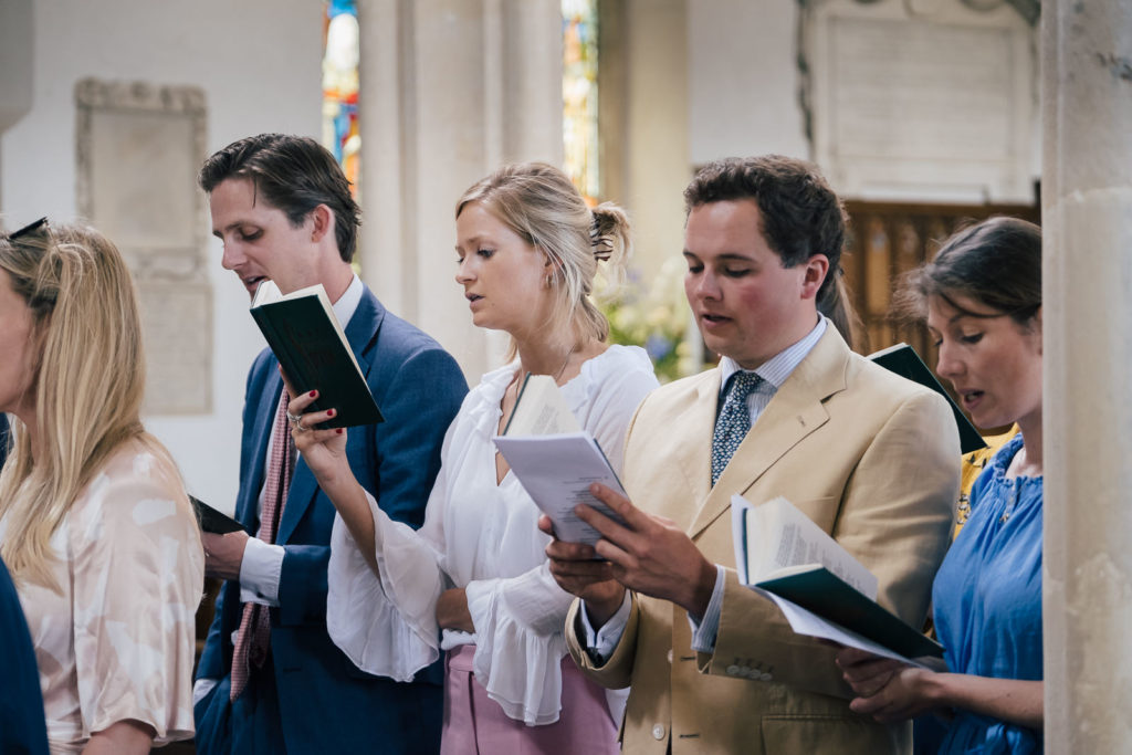 Special occasion photography with guests singing a hymn at christening service