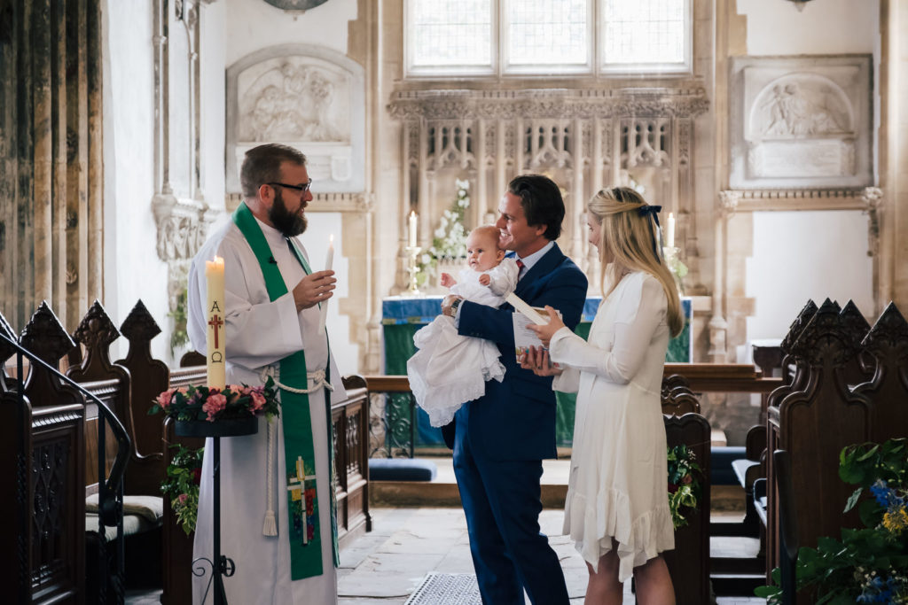 Special occasion photography with vicar talking to parents during christening ceremony