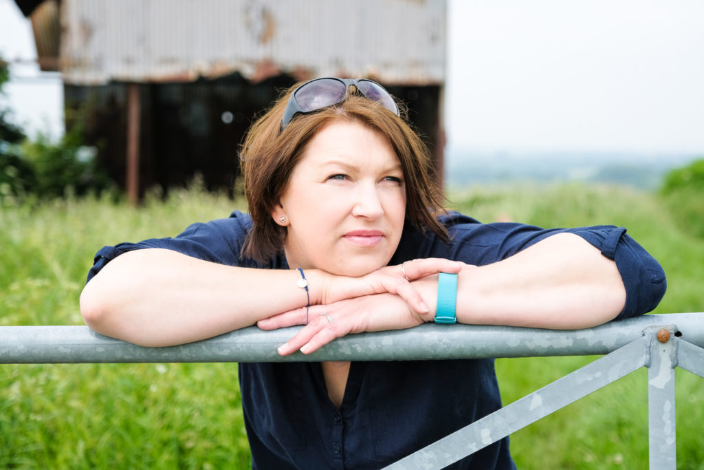 Family photography in north Wiltshire - mum relaxing and leaning on farm gate