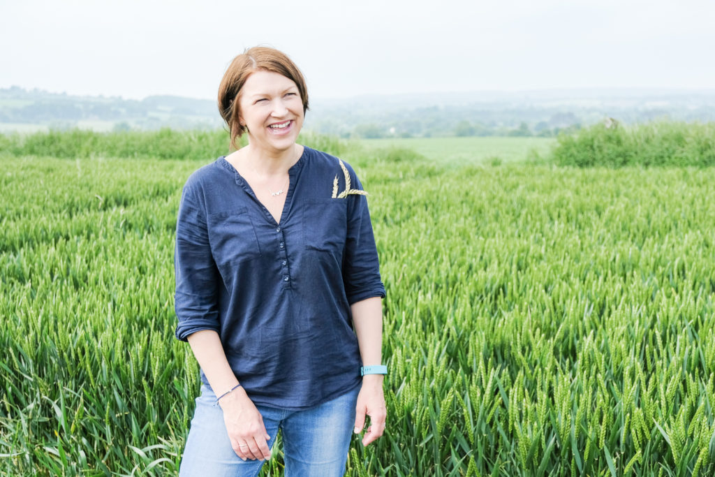 Family photography in Wiltshire - mum happy and smiling in wheat field