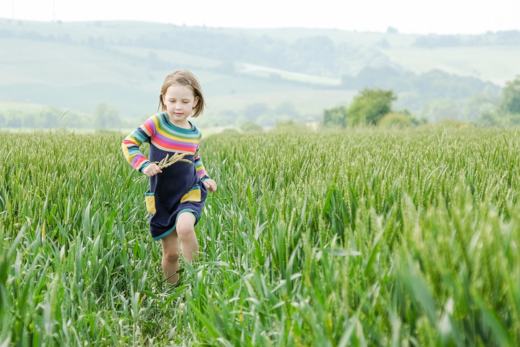 Family photography in Wiltshire with young girl in colourful dress running through field of wheat