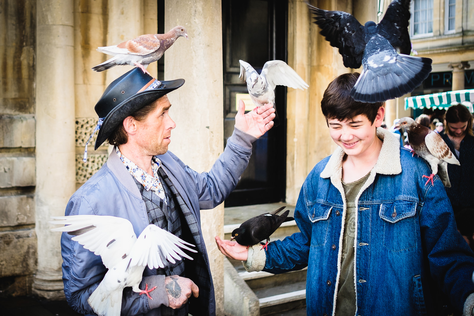 Street entertainer and teenager feeding the pigeons in Bath