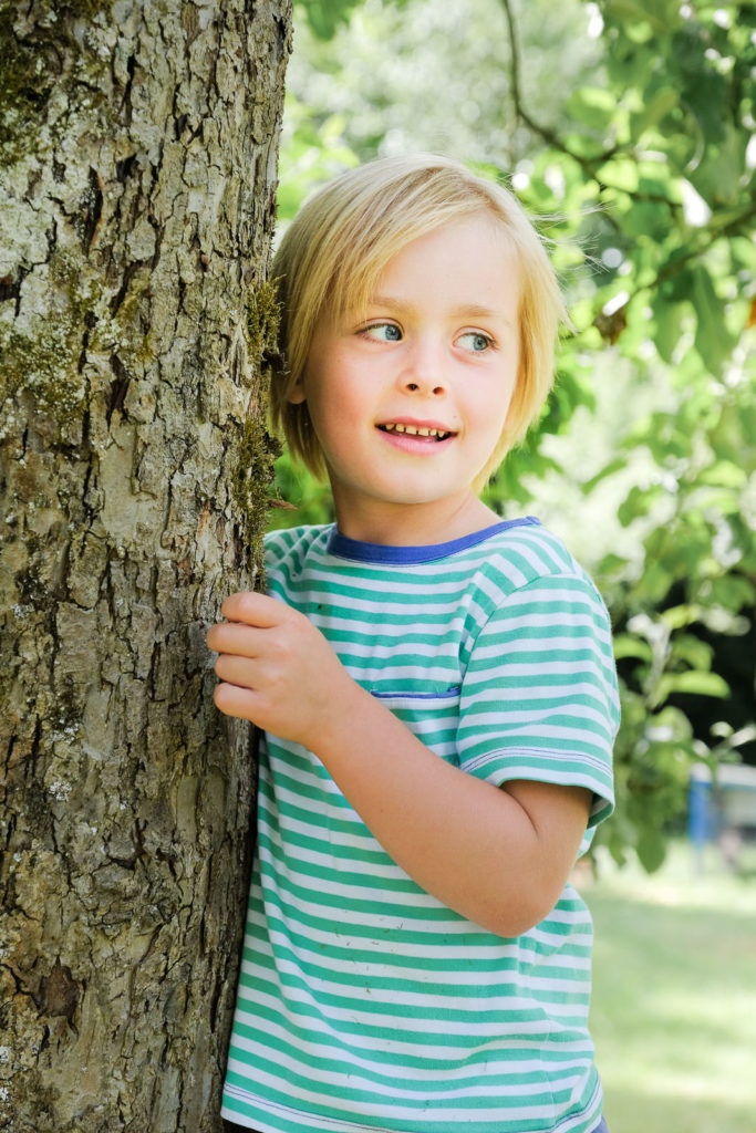 Young boy in striped top leaning against a tree