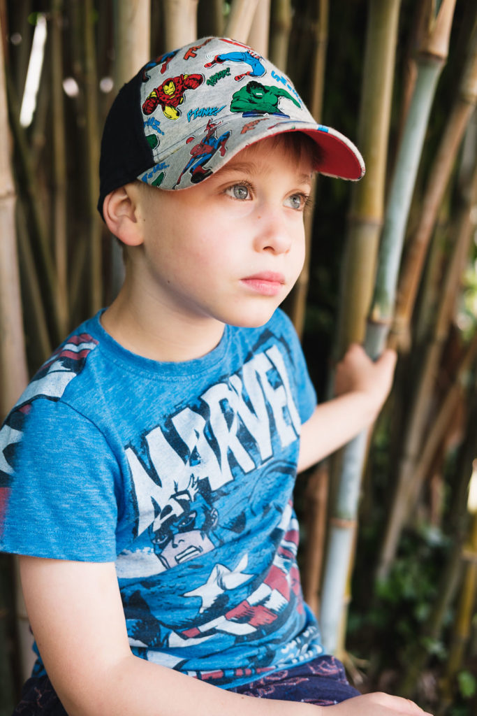 Family photography with young boy smiling wearing marvel shirt and base ball hat