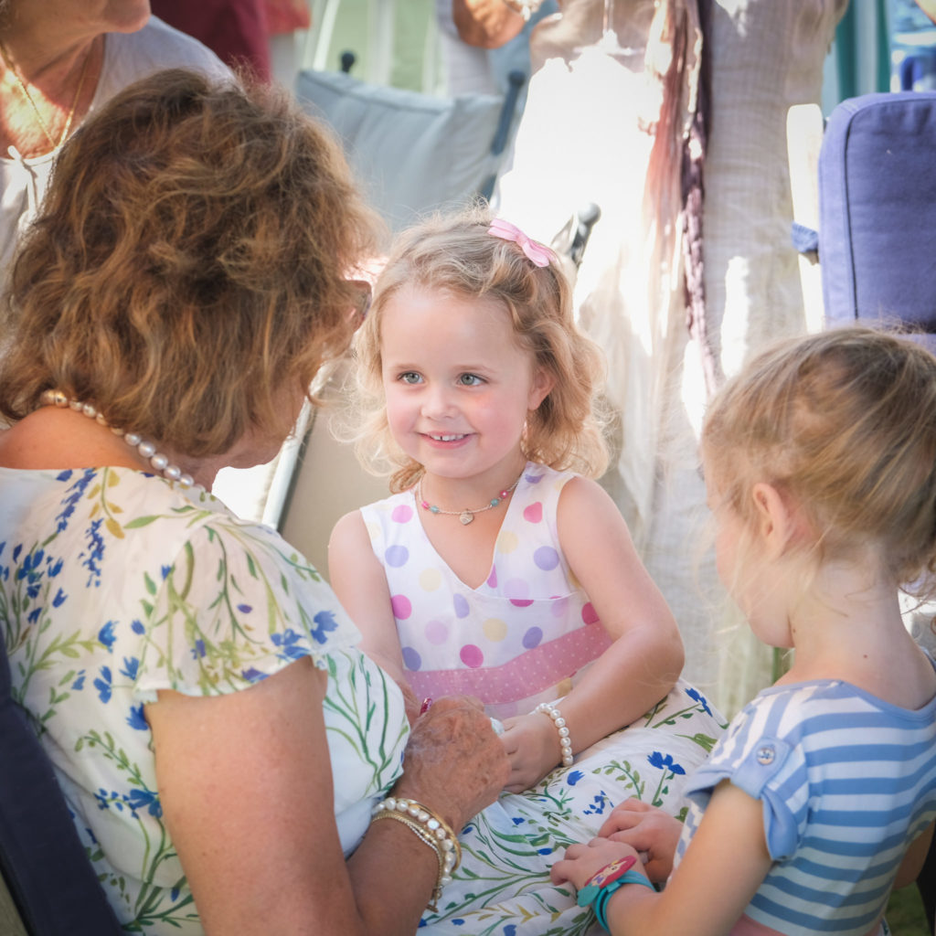 Family photography with granddaughter listening to a story from her grandmother at anniversary summer party in Bath