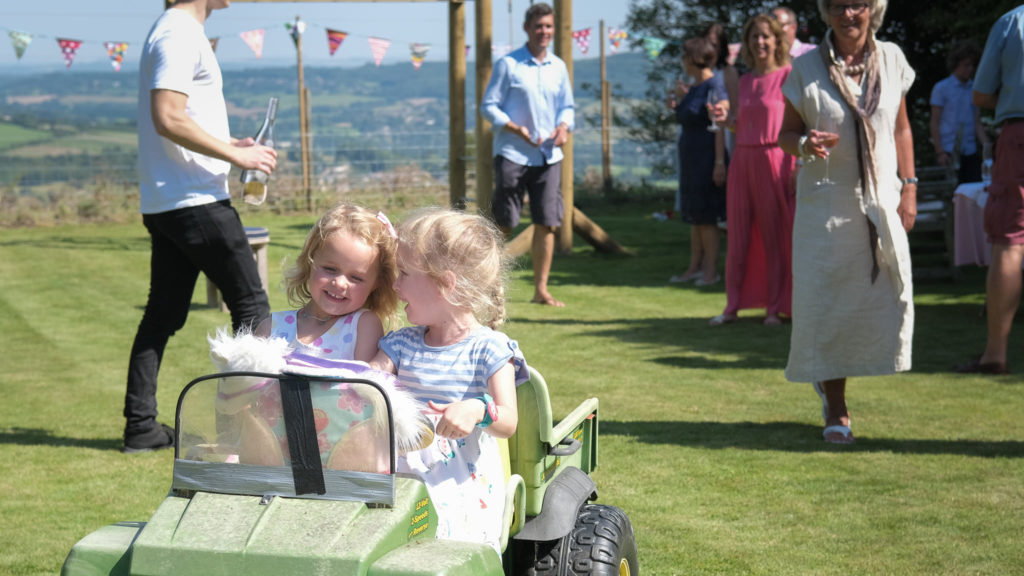 Family photography with young girls driving electric truck at anniversary party