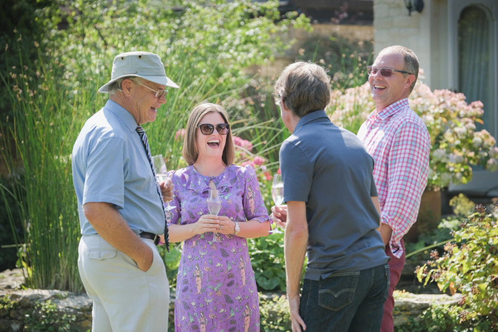 Family photography with guests having fun and chatting at summer anniversary garden party in Bath