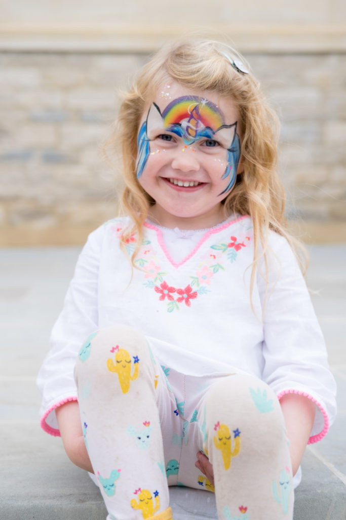 Young girl with a colourful outfit and painted face at a corporate event in Bath