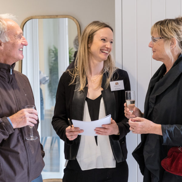 Sales team discussing property details with clients at Bath property launch