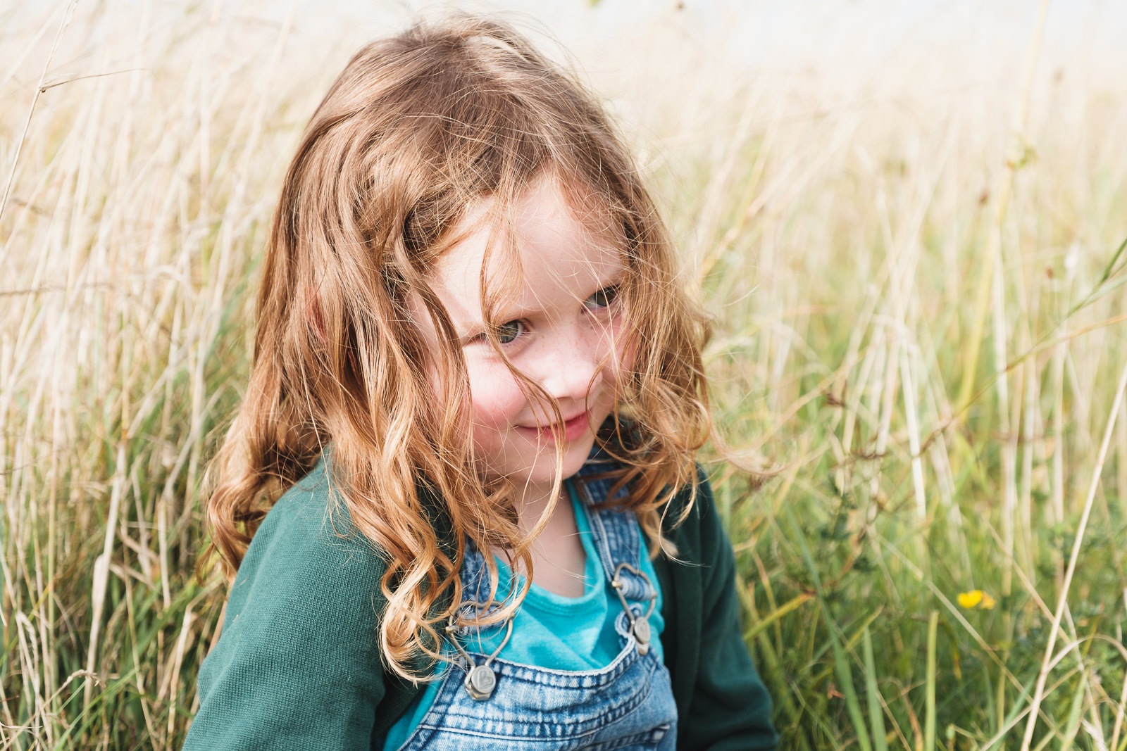 Young girl in relaxed pose in summer grass meadow with late afternoon sun