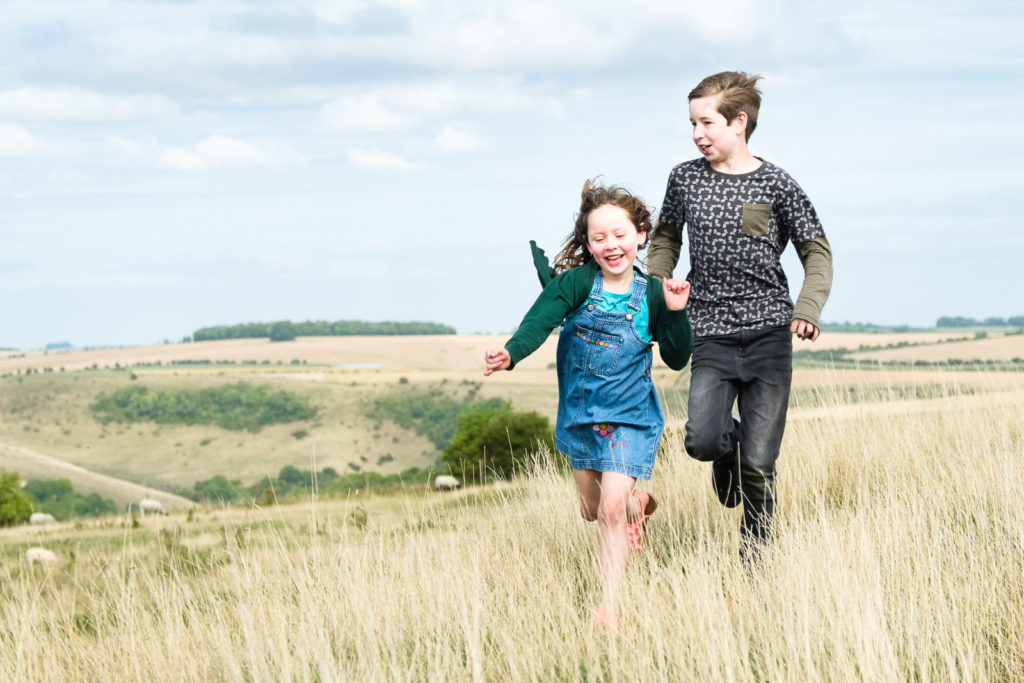Family photo session in Wiltshire with young brother and sister running outdoors