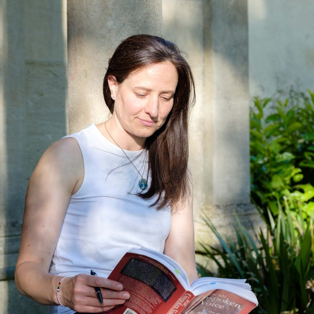 Female business owner reading a book outside in later summer sunshine