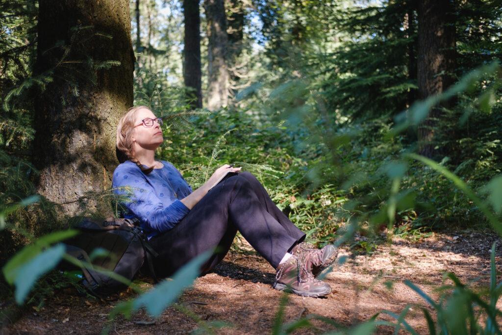 Female coach in thoughtful meditation in woodland near Bath