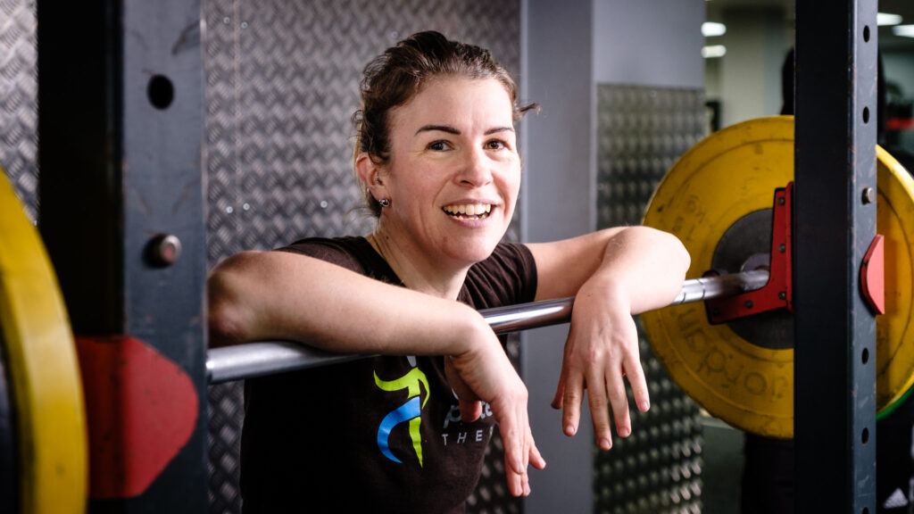 Press photo of woman taking a break during weight training session