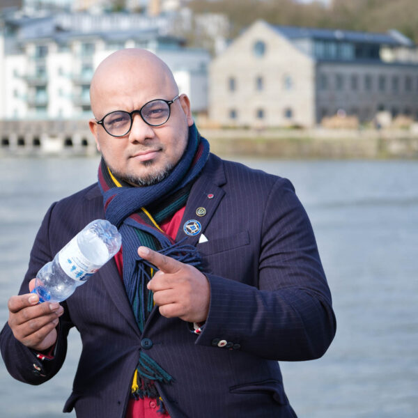 Branding photo of Naseem Talukdar holding a waste plastic bottle on the Bristol harbourside