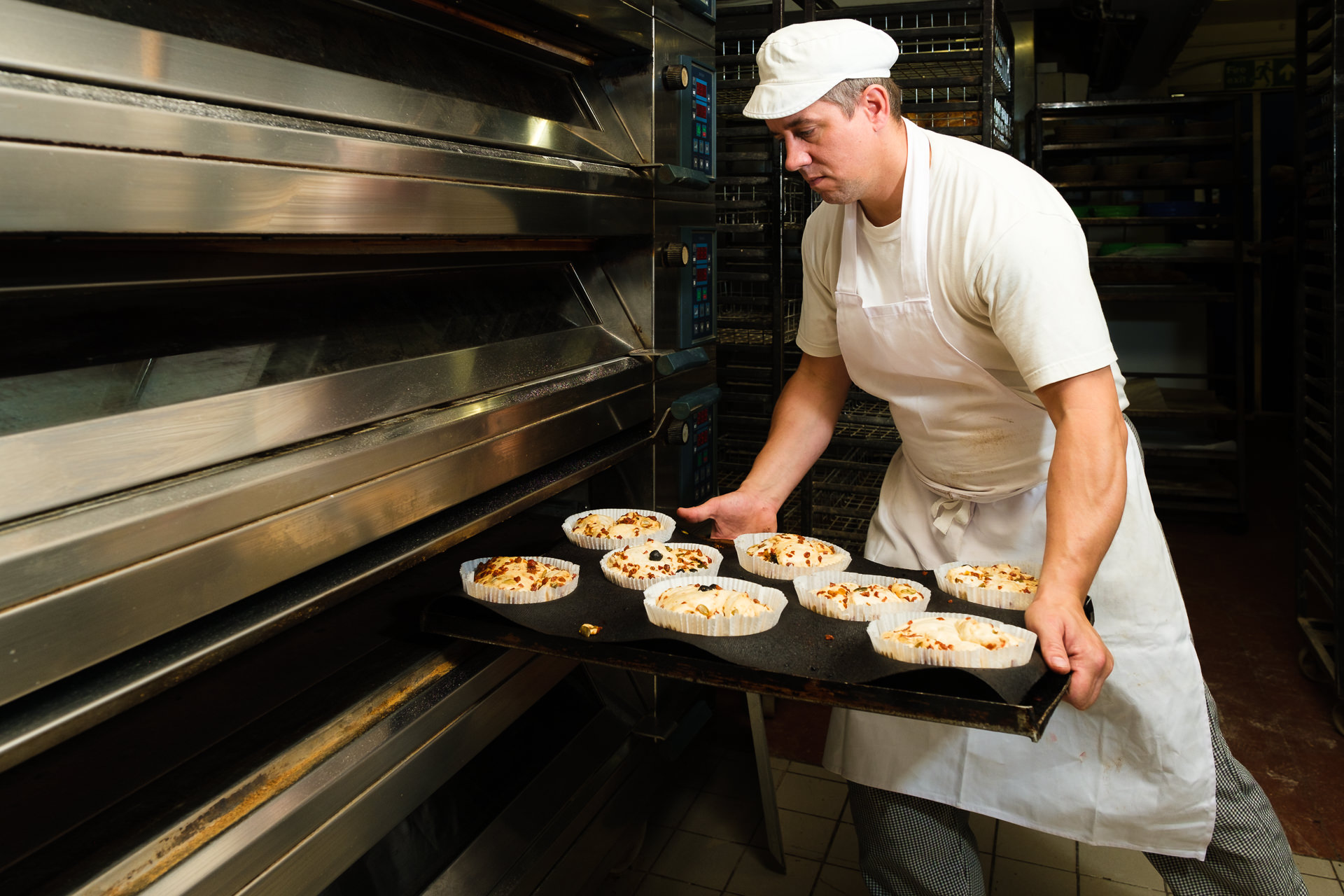 Bristol business photography with baker loading artisan breads into the oven