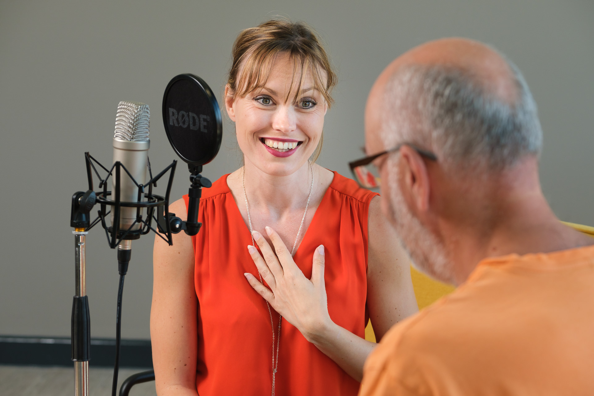 Business branding photography session with female podcast host wearing a bright orange outfit talking to a guest