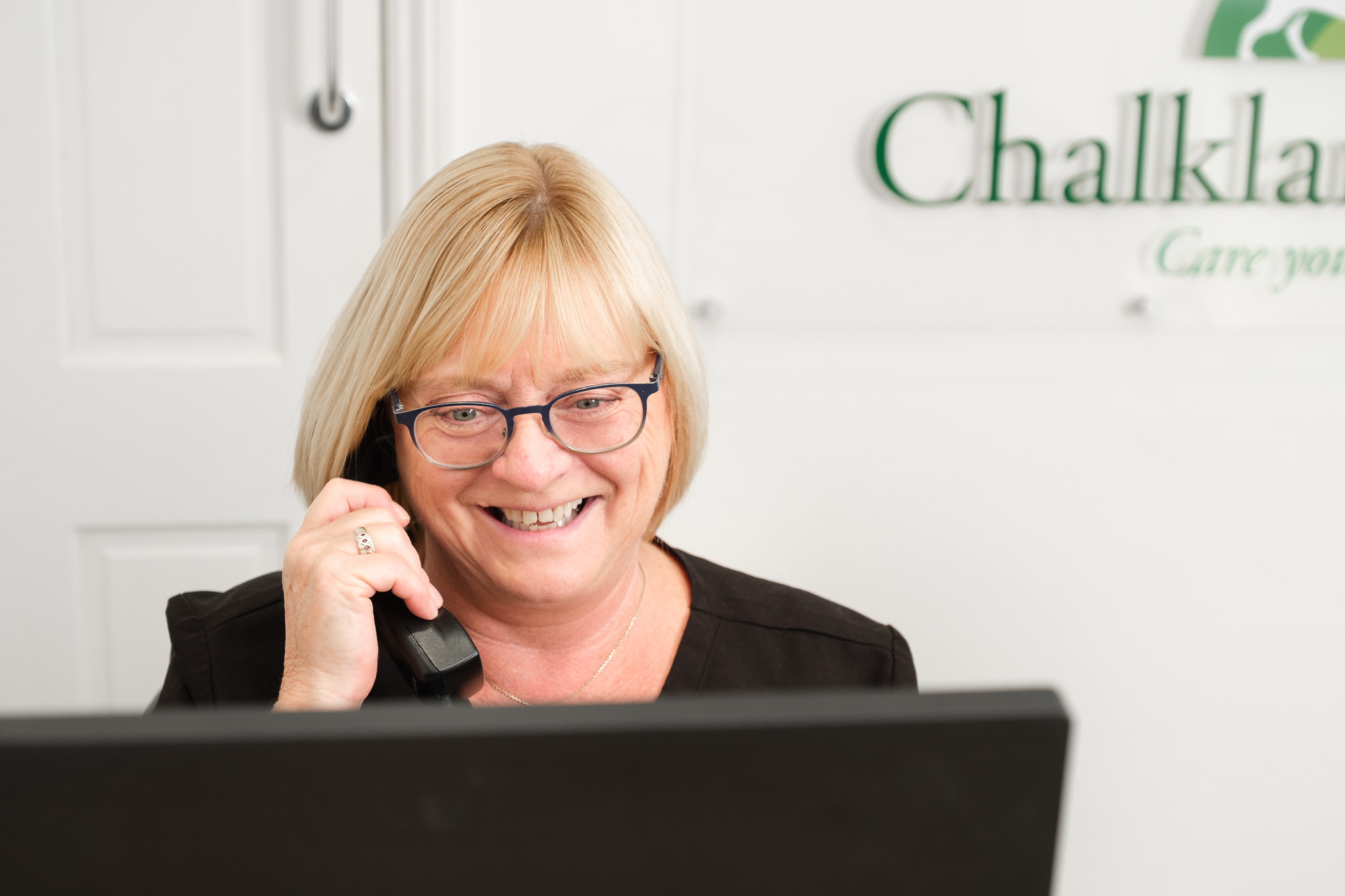 Business photography independent veterinary practice with friendly receptionist taking a call