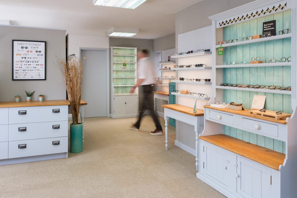 Business photography independent opticians with optician walking through bright and fresh retail space