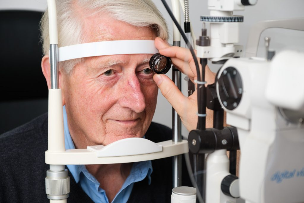 Business photography independent opticians eye test with elderly male patient